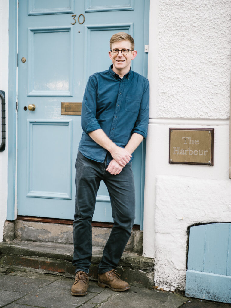 """Photograph of our CEO Sam Thomas standing outside The Harbour building in Bristol. Sam is smiling. To his right there is a plague which reads """"The Harbour"""""""