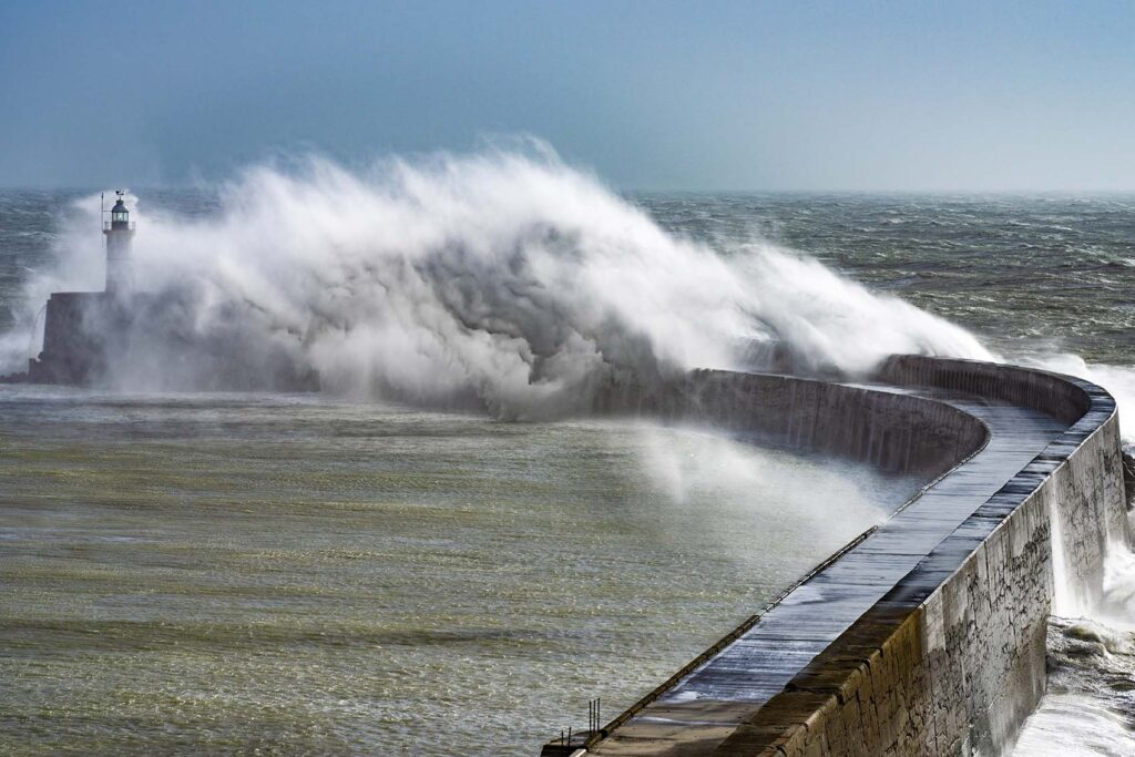 Big wave breaking over a harbour wall