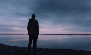 Figure stood looking over calm water. Cloudy and pink sky